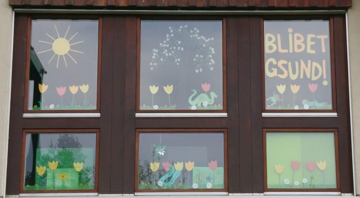Das Fenster der Speilgruppe Wahlen, bunt verziert mit Frühlingsboten wie Tulpen, einem blühenden Baum und der Sonne.